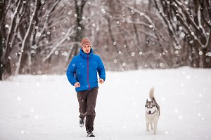 Man with husky dog at winter snowy park