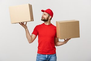 Delivery young man in red uniform holding two empty cardboard boxes isolated on white background. Copy space for advertisement