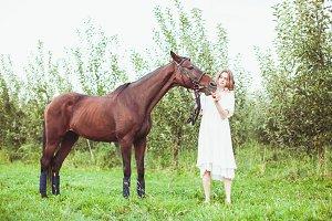 A woman feeds a horse