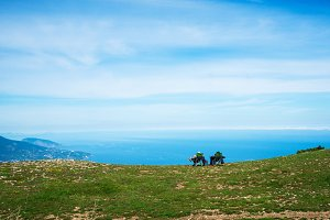Two people sit on tourist chairs on the mountain and look at the sea. Aerial panoramic view of the city of Yalta in Crimea, Russia. Ayu-Dag or Bear Mountain in the background. Landscape of the South coast of Crimea.