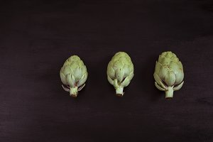 Artichokes on blak wood
