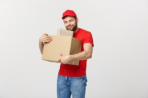 Delivery young man in red uniform huging empty cardboard boxes isolated on white background. Copy space for advertisement