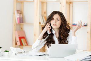 Worried stressed depressed office worker business woman receiving bad news emergency phone call at work.Looking desperate and confused.