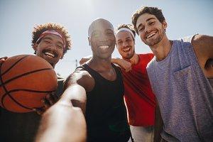 Men playing basketball posing