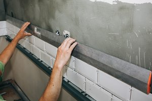 Man putting white tiles, repair work