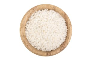 rice grains in wooden bowl isolated on white background. Top view. Flat lay