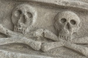 Ancient stone skull with crossbones
