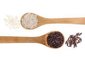 white and black rice grains in wooden spoon isolated on white background. Top view. Flat lay