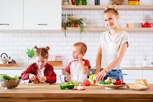 Photo of beautiful mother with daughter and son cutting vegetables at table