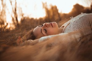 girl lying on the field on a sunset background