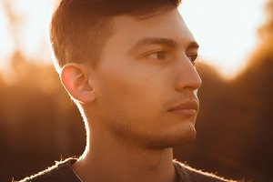 portrait of a guy in the field on a sunset background
