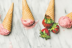 Flat-lay of homemade yogurt strawberry ice cream in waffle cones
