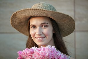beautiful happy brunette woman in hat smelling a bouquet of flowers