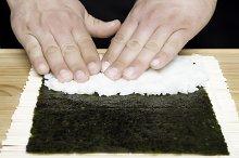 closeup hands preparing sushi