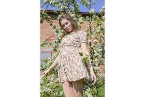 A girl in a dress in a blooming garden. Spring flowering of nature