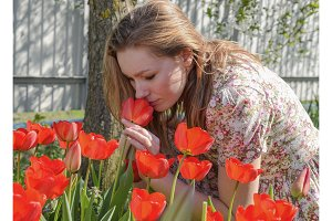 Girl sniffing tulips. The girl among the flowers.