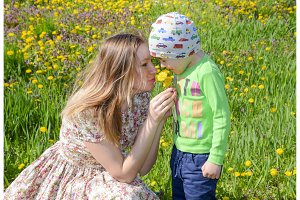 Mother walks with her son among the flowers of a dandelion. Mother and son