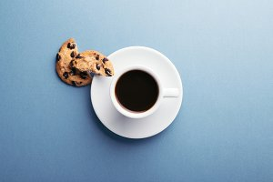 A cup of coffee and cookies.