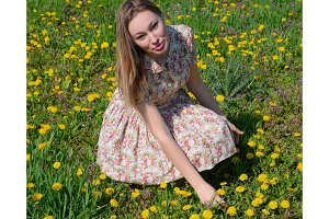 A girl in a dress in a clearing with dandelions. The girl among the flowers