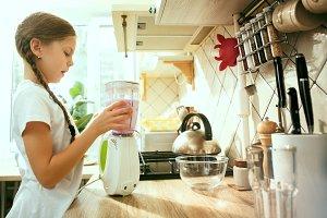 The happy smiling caucasian girl in the kitchen preparing breakfast