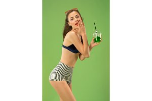 Cute girl in swimsuit posing at studio. Summer portrait caucasian teenager on green background.