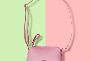 Ladies pink pastel handbag with long strap on pink background