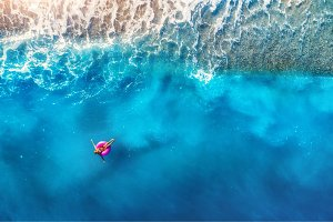Aerial view of woman swimming on the pink swim ring in the sea