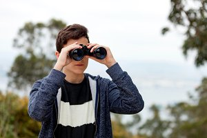 Teenager boy looking with binoculars