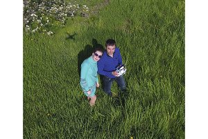 A man and a woman are photographed from a drone on a green clearing.