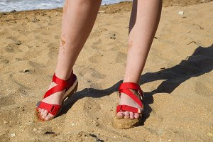 Red sandals on the legs of a girl standing on the beach sand.