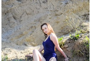 beautiful blonde in a blue bathing suit sits on a steep bank. Coast of clay and sand