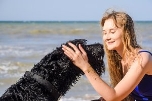 Blonde girl with a black curly dog on the beach