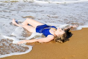 Girl in a blue bathing suit lies on the seashore and relaxes. Waves caress the girl's body
