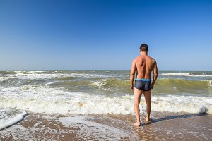 Athletic man on the beach. A man goes into the sea water