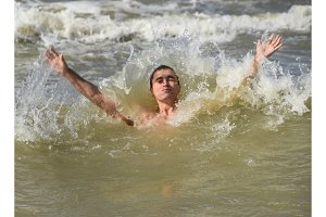 Athletic man in sea water. Bathing in the sea. A man is swimming among the waves of the sea