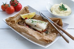 Cod fillets baked in parchment paper with vegetables