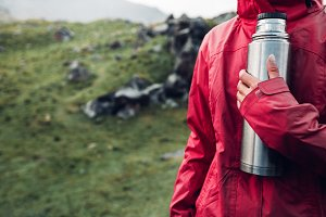 girl traveler holds a thermos in her