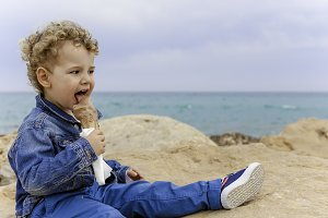 child eating ice cream on the beach