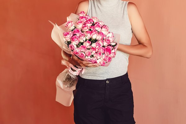 the girl is holding a bouquet of ro…