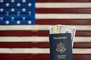 USA passport holding  a pile of dollar bills for travel concept