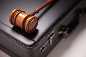 Gavel and Black Briefcase on Gradated Background with Selective Focus - Business Law Concept.