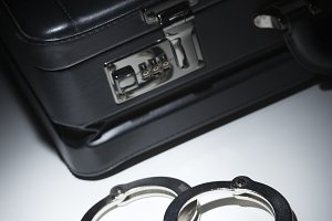 Pair of Handcuffs and Briefcase Under Spot Light Abstract.