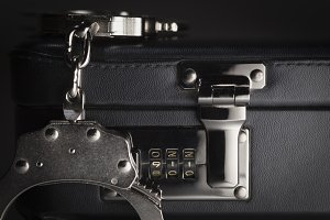 Pair of Handcuffs on Briefcase with the Numbers 911 on Lock.