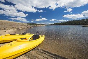 Pair of Yellow Kayaks on a Beautiful Mountain Lake Shore.
