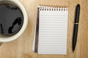 Note Pad Coffee Cup and Pen on Wood Background