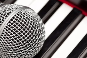 Microphone Laying on Electronic Keyboard with Narrow Depth of Field.