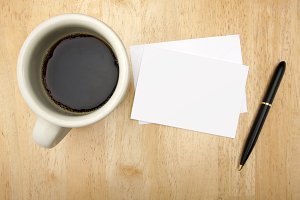 Blank Note Card, Pen and Coffee Cup on Wood Background.