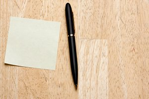 Pen and Post It Notes Pad Against a Wood Background