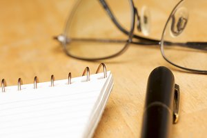 Pen, Pad and Glasses on a Wood Background with Narrow Depth of Field.