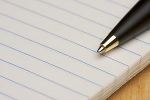 Pen and Pad of Lined Paper on a Wood Background